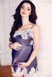 Belle femme enceinte avec les cheveux foncés posant dans la robe en soie Image libre de droits