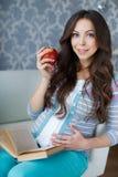 Belle femme enceinte avec un livre dans des ses mains Images stock