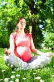 Belle femme enceinte détendant dans la pose de yoga extérieure Photo stock