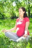 Belle femme enceinte détendant dans la pose de yoga extérieure Images stock