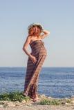 Belle femme enceinte détendant près de la mer Photos stock