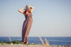 Belle femme enceinte détendant près de la mer Photographie stock libre de droits