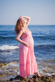 Belle femme enceinte détendant près de la mer Photographie stock