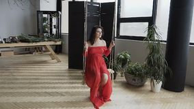 Belle femme enceinte dans une longue robe rouge balançant sur l'oscillation dans un studio élégant avec de grandes fenêtres banque de vidéos