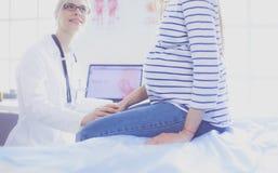 Belle femme enceinte de sourire avec le docteur à l'hôpital photographie stock