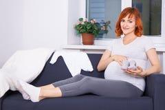 Belle femme enceinte s'asseyant avec des articles d'habillement pour le nouveau Images libres de droits