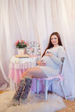 Belle femme enceinte s'asseyant sur une chaise et Images libres de droits