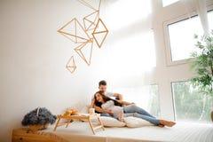 Belle femme enceinte se trouvant sur le grand lit avec le mari Image libre de droits