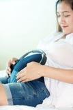 Belle femme enceinte tenant des écouteurs Image stock