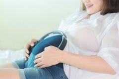 Belle femme enceinte tenant des écouteurs Image libre de droits