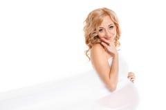 Belle femme enceinte tenant l'oreiller rouge de coeur dans des ses mains d'isolement sur le fond blanc Photo stock