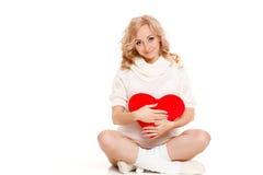 Belle femme enceinte tenant l'oreiller rouge de coeur dans des ses mains d'isolement sur le fond blanc Images stock