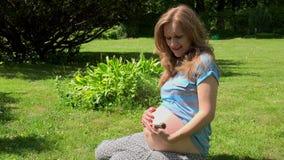 Belle femme enceinte tenant le grand escargot sur sa main banque de vidéos