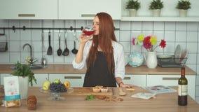 Belle femme essayant le vin rouge à la cuisine moderne Fille principale rouge banque de vidéos