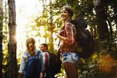Belle femme et amis trimardant dans la forêt Photos libres de droits