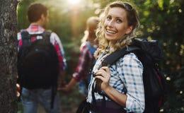 Belle femme et amis trimardant dans la forêt Photographie stock libre de droits