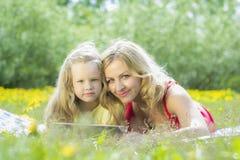 Belle femme et fille jouant sur un comprimé Image stock