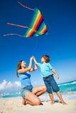 Belle femme et garçon tenant des bras avec le cerf-volant Photographie stock libre de droits