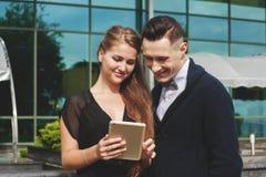 Belle femme et homme regardant le PC de comprimé Photo libre de droits