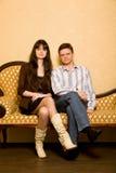 Belle femme et homme s'asseyant sur le sofa dans la chambre Photo libre de droits