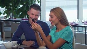 Belle femme et son ami lisant quelque chose au téléphone intelligent banque de vidéos