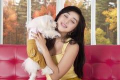 Belle femme et son chien à la maison Photo stock