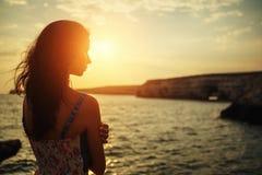 Belle femme examinant la distance le coucher du soleil contre le ciel images libres de droits
