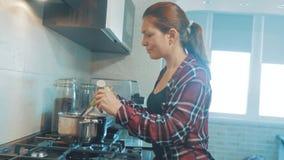 Belle femme faisant cuire et examinant la nourriture dans la cuisine la fille dans la cuisine verse le poivre râpé dans la soupe clips vidéos