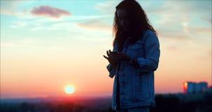 Belle femme faisant la forme de coeur avec des mains ? la fille de coucher du soleil retardant le geste de symbole d'amour avec l banque de vidéos