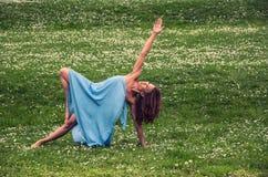 Belle femme faisant le yoga sur le pré photographie stock libre de droits