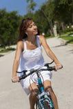 Belle femme faisant un cycle dans la robe de Sun blanche Images libres de droits
