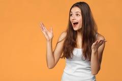 Belle femme heureuse étonnée regardant en longueur dans l'excitation, d'isolement sur le fond orange photos libres de droits