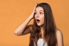 Belle femme heureuse étonnée regardant en longueur dans l'excitation D'isolement sur le fond orange photographie stock libre de droits