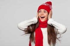 Belle femme heureuse étonnée regardant en longueur dans l'excitation Fille de Noël utilisant le chapeau tricoté et l'écharpe chau images libres de droits