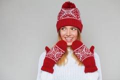 Belle femme heureuse étonnée regardant en longueur dans l'excitation Fille de Noël utilisant le chapeau tricoté et les mitaines c image libre de droits