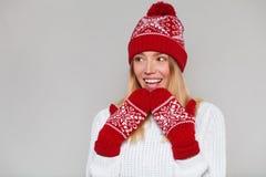 Belle femme heureuse étonnée regardant en longueur dans l'excitation Fille de Noël utilisant le chapeau tricoté et les mitaines c photo libre de droits