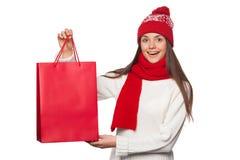 Belle femme heureuse étonnée tenant le sac rouge dans l'excitation, faisant des emplettes Fille de Noël en vente d'hiver avec le  photographie stock libre de droits