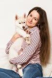 Belle femme heureuse étreignant le chien de traîneau de chiot fille s'asseyant sur un sofa avec un chien Photographie stock