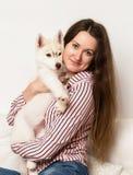 Belle femme heureuse étreignant le chien de traîneau de chiot fille s'asseyant sur un sofa avec un chien Images libres de droits
