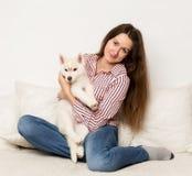 Belle femme heureuse étreignant le chien de traîneau de chiot fille s'asseyant sur un sofa avec un chien Photos libres de droits