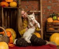 Belle femme heureuse avec le chiot enroué avec la récolte d'automne sur un fond de mur de briques Photos libres de droits