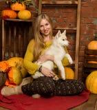 Belle femme heureuse avec le chiot enroué avec la récolte d'automne sur un fond de mur de briques Photo libre de droits