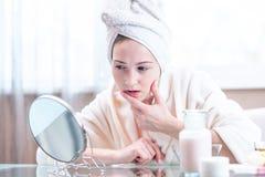 Belle femme heureuse avec une serviette sur sa tête regardant sa peau dans un miroir Concept d'hygiène et d'entretenir la peau photographie stock libre de droits