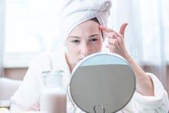 Belle femme heureuse avec une serviette sur sa tête regardant sa peau dans un miroir Hygiène et entretenir la peau images libres de droits