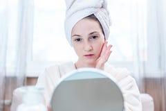 Belle femme heureuse avec une serviette sur sa tête regardant sa peau dans un miroir Hygiène et entretenir opportuns la peau images stock