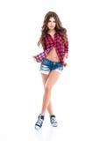 Belle femme heureuse dans la chemise à carreaux, les shorts de jeans et des espadrilles Images libres de droits