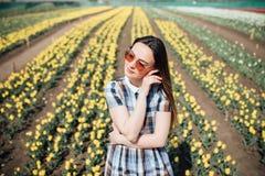 Belle femme heureuse dans un domaine du sourire jaune de tulipes Images libres de droits