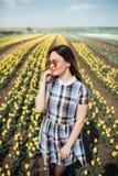 Belle femme heureuse dans un domaine du sourire jaune de tulipes Photos libres de droits