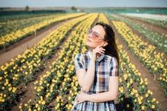 Belle femme heureuse dans un domaine du sourire jaune de tulipes Photographie stock libre de droits