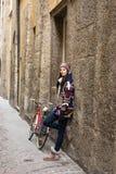 Belle femme heureuse dans une petite allée, rue avec un vieux vélo Photos libres de droits